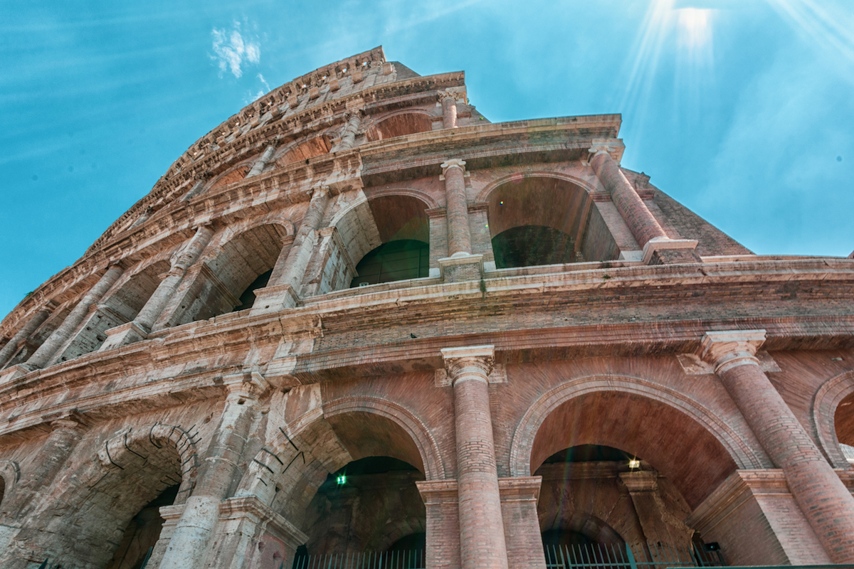 Colleseum glowing with sun light with blue sky . Rome Italy